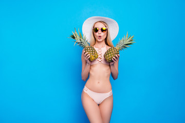 Wall Mural - Portrait of comic funny girl with slender figure in pink two pieces swimsuit closing tits with two pineapples isolated on bright blue background. Pop grimace concept