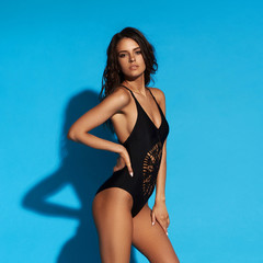 Young sexy slim tanned woman in black swimsuit posing against blue background. Full length fashion...