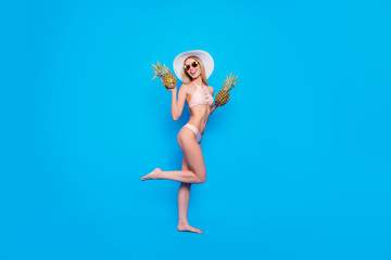 Fullbody concept of pretty fit girl in eyewear two pieces swimsuit holding raised thin leg having two fresh pineapples in hands enjoying sunshine isolated on bright blue background