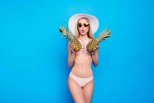 Portrait of comic funny girl with slender figure in pink two pieces swimsuit closing tits with two pineapples isolated on bright blue background. Pop grimace concept