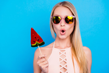 Wall Mural - Pop nutrition healthy lifestyle calories concept. Portrait of shocked wondered girl in eyewear holding sweet piece of watermelon on stick isolated on vivid blue background