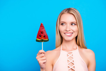 Portrait of funny excited girl looking at sweet tasty piece of watermelon on stick biting low lip isolated on bright blue background. Confectionery calories healthy nutrition concept