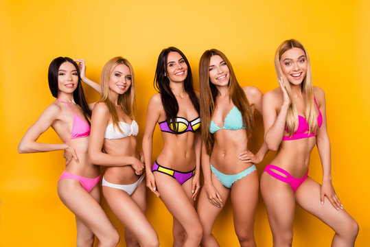 Summer, holiday, beach, pool, togetherness, joy time. Seductive five young ladies in swim wear are posing. Their figures are ideal, hairstyle and skin are so perfect and healthy, shining and smooth
