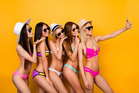 Cheers! Selfie mania! Five young lovely hot ladies in sunglasses, trendy swimming wear and caps are posing for a selfie shot, blond is taking. They are so playful, flirty, making memories