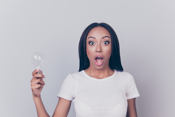 Incredible! Portrait of beautiful amazed astonished shocked surprised clever intelligent smart pretty afro brunette woman holding bulb in hand big eyes tanned bronze skin isolated on gray background