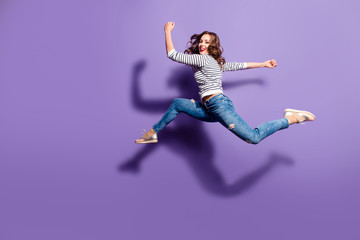 Portrait of fit sporty girl jumping over in the air looking at camera having good stretching isolated on violet background, people life energy lifestyle powerful concept
