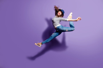 Portrait of active pretty girl in action jumping in the air demonstrate perfect stretching making athletic pose isolated on violet background