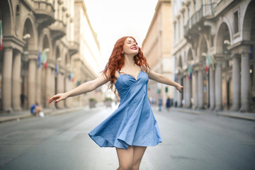 Beautiful girl enjoying her feelings, swinging in the street
