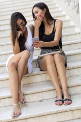 Two beautiful women looking at phone