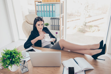 Portrait of successful trendy woman putting legs on table wearing stilettos watching video movie drinking tea holding mug and saucer sitting at desktop in modern office