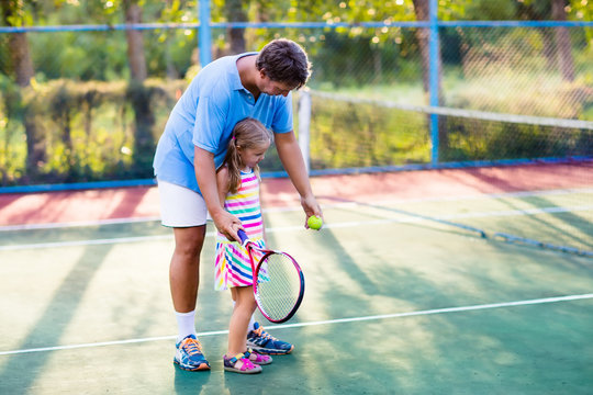 Family playing tennis on outdoor court