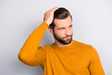 Close up portrait of attractive handsome virile masculine brutal guy combing back his long brown-haired furfur looking aside wearing color of mustard tight pullover isolated on gray background