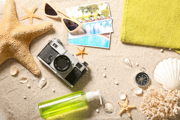 Photo camera, beach accessories and sea shells on sand