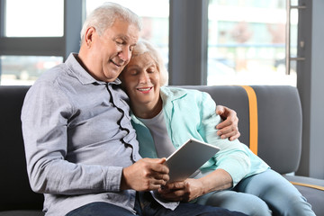 Happy senior couple with tablet PC sitting on sofa at home