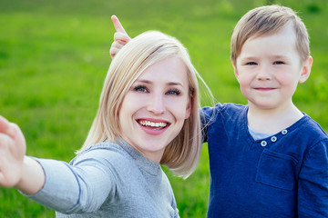 attractive mother (female person) and little boy take pictures selfie on phone in the park on a background of green grass and trees