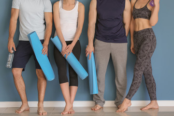 Group of people with yoga mats near color wall