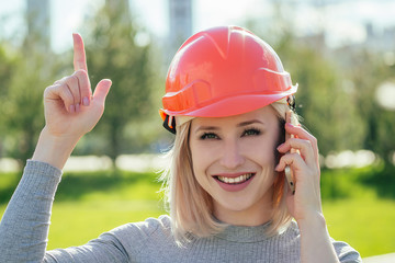 attractive blonde boss woman builder in an orange helmet in the park on a background of green grass