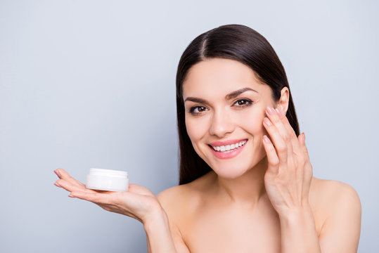 Enhancement perfection rejuvenation revitalization moisturizing concept. Portrait of pretty woman presenting face cream in white jar on palm applying mask for flawless skin isolated on grey background