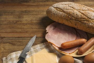 various ingredients for breakfast on wood background, bread, egg, sausage, ham, and cheese set on background