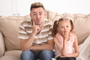 Funny father and daughter sitting on sofa at home
