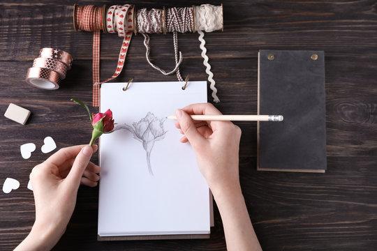 Woman drawing beautiful rose on sketch pad