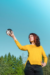 The whole world in her hand: Young woman in stylish yellow pullover holding earth in her hand in front of sky and trees. Save the earth concept.