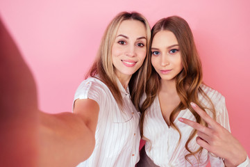 two beautiful and smiling female persons (mother and daughter) take photos selfie on the phone on a pink background in the studio. concept of love and family