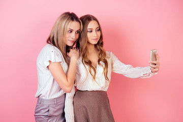two beautiful and smiling girlfriends (mother and daughter) take photos selfie on the phone on a pink background in the studio. concept of selfishness and self-love