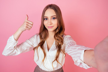 beautiful and smiling girl teenager makes photos selfie on the phone on a pink background in the studio. concept of selfishness and selfishness