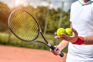 Close up photo of young man on tennis court. Man playing tennis. Man is ready to throw tennis ball. Beautiful forest area as background