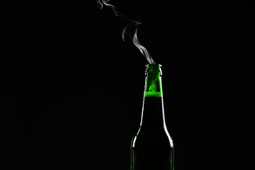 Glass bottle of cold beer on dark background