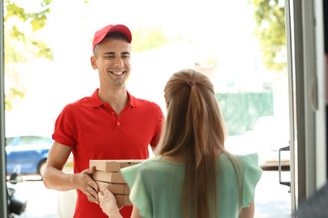Young man giving pizza boxes to woman at doorway. Food delivery service