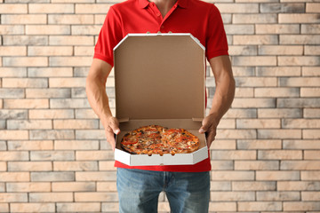 Young man holding box with tasty pizza against brick wall. Food delivery service