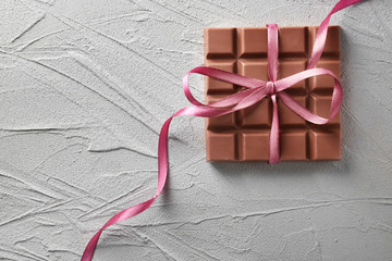 Tasty milk chocolate bar with ribbon on textured background