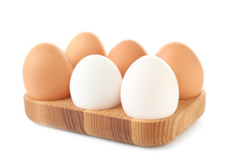 Wooden holder with chicken eggs on white background