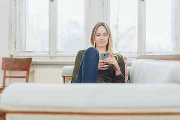 Young woman relaxing on a sofa with a mobile