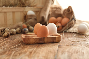 Wooden holder with chicken eggs on table