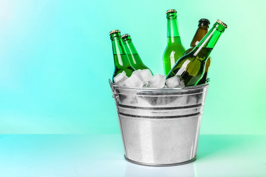 Bottles of beer in ice bucket on color background