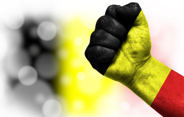 Flag of Belgium painted on male fist, concept of conflict