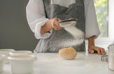 Woman sifting flour on dough in kitchen