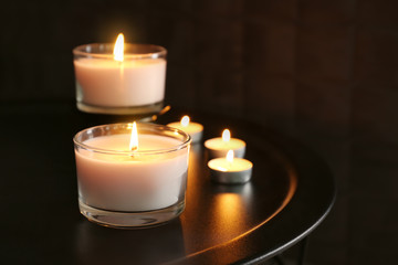 Burning wax candles on table in darkness