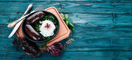 Poached egg with spinach and buckwheat sausage. On a wooden background. Top view. Copy space.