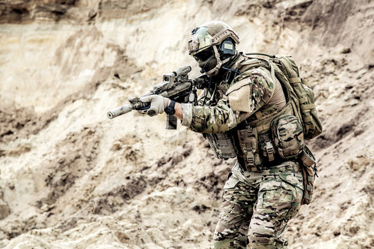 Army infantryman, special forces soldier with hidden face, protected opscore helmet and body armor, equipped tactical radio headset, in ocp camouflage uniform, aiming with service carbine in hands