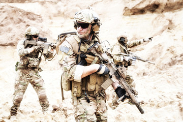 Group of well equipped US army commandos armed with assault rifles, moving through sandy terrain or desert. Military reconnaissance team secret operation, special forces mission on enemy territory