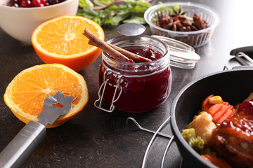 Jar with delicious cranberry sauce and products on table