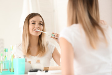 Beautiful young woman brushing her teeth in morning