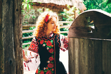 Young Slavonic woman in traditional embroidered costume at the gate