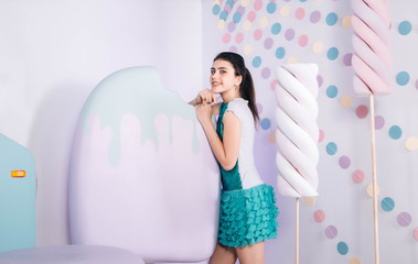 photo zone with sweets and ice cream. photo zone with sweets and ice cream. pretty brunette wearing green fashion dress