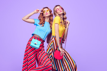 Wall Mural - Two Playful Sisters Friends Jumping in Studio on Purple. Young Beautiful Model Woman with Blowing lips Expression in Fashion Trendy Outfit. Crazy Blond Redhead Girls Having Fun