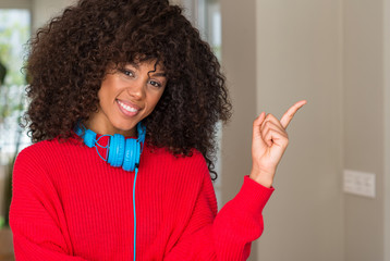 African american woman wearing headphones with a big smile on face, pointing with hand and finger to the side looking at the camera.